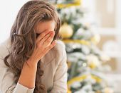stock photo of stress  - Stressed young woman in front of christmas tree - JPG