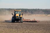 Farmer Cultivating Field With Caterpillar Challenger Tractor And Cultivator