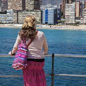 Beautiful Lady Gazes Over Playa De Levante, Benidorm, Spain.