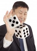 Adult asian business man a suit playing dice isolated