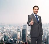 business, gesture and office concept - handsome buisnessman showing thumbs up