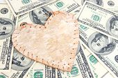 Love and money concept. Heart and American currency close up