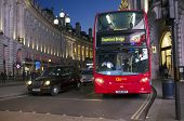 LONDON, UK - APRIL 16, 2014: London transport, Black taxi cab and red double-decker bus at Piccadill