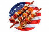 Genuine American Chicken, Onion, and Bell Pepper Shish Kebab on Metal Skewers with Wooden handles on an American Flag Plate.  Kebab is a Middle Eastern dish of pieces of meat, on a skewer.