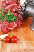raw fresh beef meat fillet on a wooden plate with dill , hot green red peppers, and grinder isolated over white background