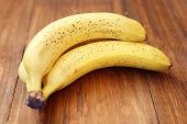 stock photo of bunch bananas  - bunch of ripe fresh bananas on a wooden background - JPG