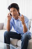 Annoyed man sitting on couch talking on phone at home in the living room