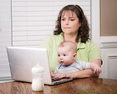Mother Holding Baby While Working On Her Computer