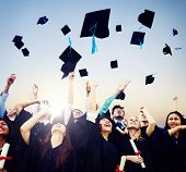 stock photo of cheers  - Cheerful students throwing graduation caps in the Air - JPG
