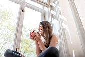Young And Cute Lady Sitting On The Windowsill And Looking Out The Window With Cup Of Coffee In The M