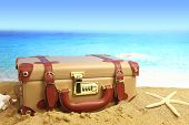 Closed suitcase on beach background