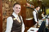 Happy female receptionist worker standing at hotel counter