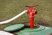 stock photo of firehose  - Red fire hydrant stands on roadside in manhole - JPG