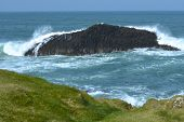 Waves crashing against an island of rock