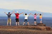 Family holding hands and arms up enjoying view of landscape on vacation