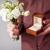 Happy Man Holding An Engagement Ring Box In His Hand And A Bouquet Of Flowers