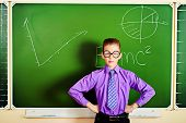 Smart schoolboy stands at the blackboard in the classroom with opened book. Education.