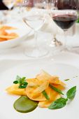 Ravioli with pesto sauce and potato chips on restaurant table