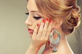 stock photo of jewelry  - Beautiful model with red nail Polish and elegant hairstyle - JPG