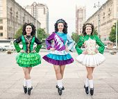 Three Women In Irish Dance Dresses Posing