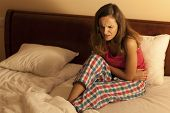Woman In Bed Having Abdominal Cramps