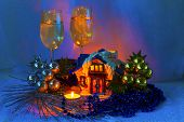 Christmas Arrangement With Ceramic House With Candles And Two Of Groceries With Champagne.