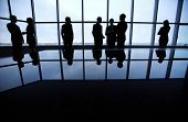 Silhouettes of business people standing against a panoramic window in office