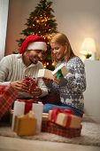 Cheerful couple opening giftboxes on Christmas night
