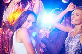 Energetic young people dancing in night club
