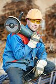Construction builder worker portrait with grinder machine for cutting metal reinforcement rebar rods at building site