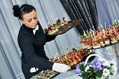 Waiter with meat dish serving catering table with food snacks during party event