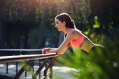 Attractive brunette resting after fitness training outdoors