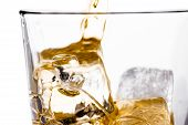 Beginning Pouring Scotch Whiskey In Glass With Ice Cubes On White