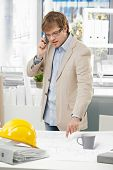 Young caucasian engineer talking on mobile phone and pointing at plan at office. Folder and hardhat