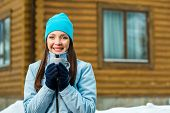 Portrait of woman drinking tea and wearing warm clothes outdoors when going in for winter sports