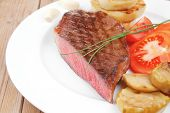 meat savory : grilled beef fillet mignon served on white plate with tomatoes and potatoes on wooden