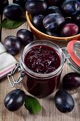 Plum Jam And Plums On Wooden Background.