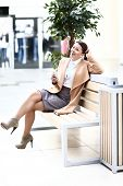 Full length of young woman with phone sitting in shopping centre