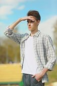 Young Man Looking Into The Distance On A Hot Sunny Summer Day Outdoors