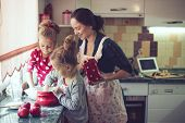 image of little kids  - Mother with her 5 years old kids cooking holiday pie in the kitchen to Mothers day - JPG