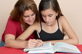 Hispanic teenage girl studying with her mother at home