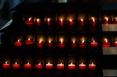 Large Group Of Burning Candles At A Black Background In The Church.