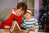 Father And Little Son Preparing A Gingerbread Cookie House
