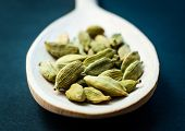 Whole cardamom in wooden spoon on dark background