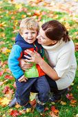 Young Mum And Her Little Kid Son Hugging Together In Autumn Park