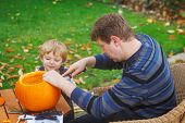 Young Man And Toddler Boy Making Halloween Pumpkin