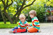 Two Little Children Playing With Red School Bus