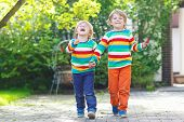 Two Little Sibling Kid Boys In Colorful Clothing Walking Hand In Hand