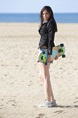 Tough looking woman walking on a beach, carrying a skateboard behind her back