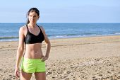 Strong, fit, sporty woman, wearing a sports bra and fluorescent shorts, standing on a beach during a short break of her training run, with her hand on her hip